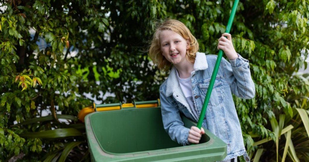crutis cleaning the inside of a green wheelie bin